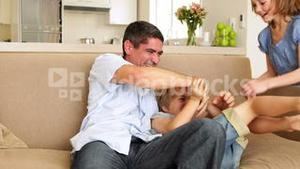 Father and daughter tickling little boy in the couch