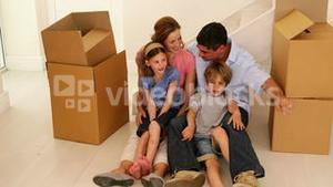 Happy family sitting on floor in their new home