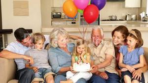 Extended family celebrating little girls birthday on couch
