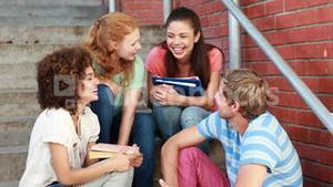 Happy students sitting on steps chatting