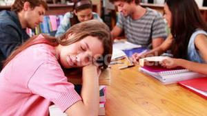 Students studying together in the library with girl sleeping on books