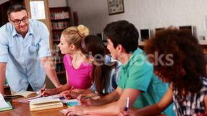 Young students revising in the library with their teacher