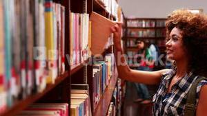 Pretty student picking out a book in library