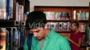 Handsome student picking out a book in the library