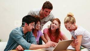 Cheerful students using laptop together