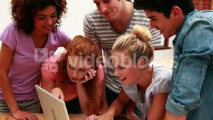 Cheerful young students using laptop together