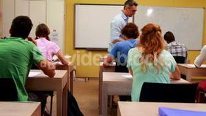 Lecturer handing out assignments to his students in classroom