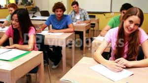 Students smiling and giving thumbs up to camera in classroom