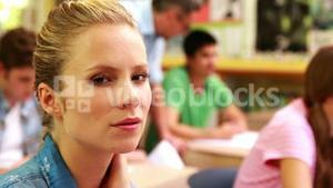 Focused student smiling to camera in classroom