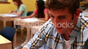 Handsome student smiling to camera in classroom