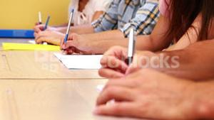 Students sitting in a line taking notes in classroom