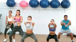 Fitness class lifting kettle bells together