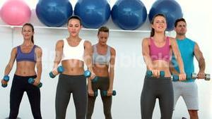 Fitness class lifting dumbbells together