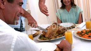 Grandfather carving chicken at dinner table