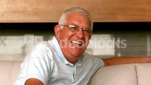 Senior man smiling at camera on couch