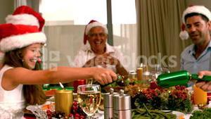 Siblings pulling a christmas cracker at the dinner table