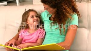 Mother and daughter reading book on the couch