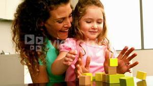 Mother playing with daughter with blocks
