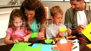 Parents and children making paper shapes together at the table