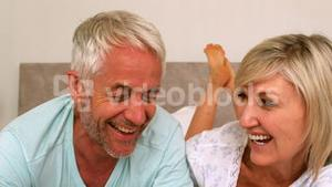 Couple laughing together on bed