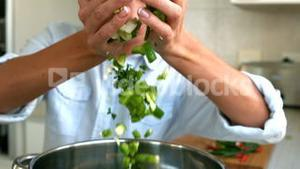 Woman adding chopped vegetables to pot
