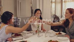 Women toasting with white wine at dinner