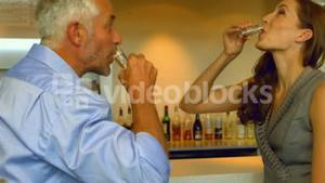 Business colleagues drinking a shot together