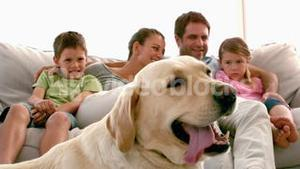 Family sitting on the couch with labrador dog in foreground