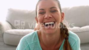Woman lying on rug using tablet and laughing