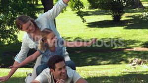 Family playing airplanes in the park