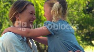 Young mother giving her daughter a hug in the park