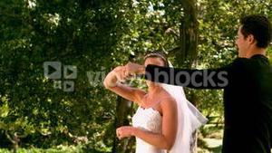 Happy newlywed couple dancing in the park
