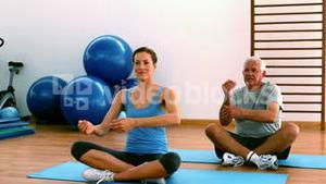 Elderly man sitting on mat exercising with instructor