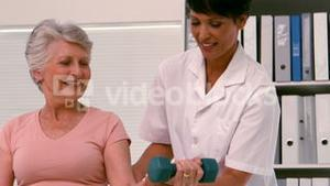 Physiotherapist helping patient lift hand weight