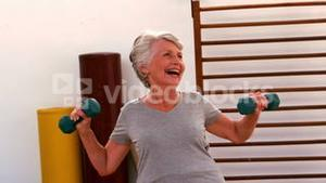 Elderly woman working out with dumbbells