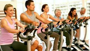 Happy spinning class in fitness studio
