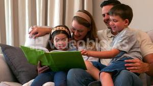 Happy young family looking at photo album together