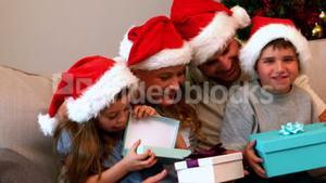 Happy young family opening christmas presents on couch