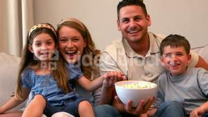 Happy family watching television eating popcorn