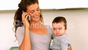 Mother holding her baby son in the kitchen talking on phone