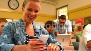 Blonde student texting on her phone in class