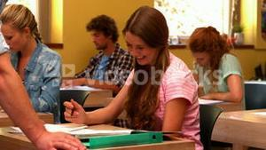 Happy student being helped by teacher in the classroom
