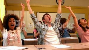 Excited students cheering in classroom