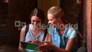 Happy students sitting using tablet pc