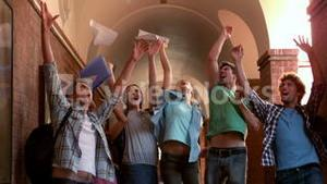 Happy students jumping in the air in a hallway