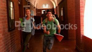 Happy students running through a hallway