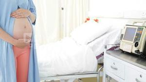 Pregnant woman standing in hospital gown