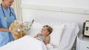 Nurse trying to cheer up a sick little girl