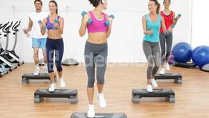 Aerobics class stepping together led by instructor and lifting dumbbells