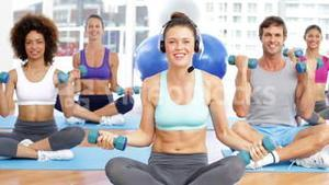 Fitness class sitting together and lifting dumbbells